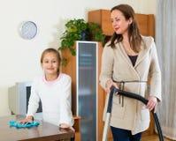 妇女和女儿清洗房子 免版税图库摄影