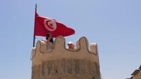 妇女和女孩挥动的手和看对从塔上面的照相机与突尼斯旗子的 影视素材