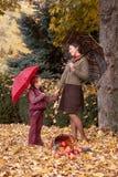妇女和女孩有伞的在秋天室外森林的画象,黄色叶子背景 免版税库存图片