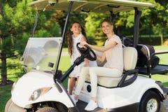 妇女和女孩白色高尔夫车的 女孩得到了位子并且今后偷看 免版税库存图片