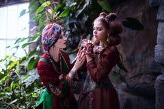 妇女和女孩画象种族衣裳的在热带庭院里 库存图片