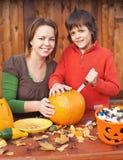 妇女和她的儿子为万圣夜做准备 免版税库存照片