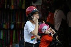 妇女和她的女儿中止和公园摩托车电话的在Sampheng贸易镇 库存照片