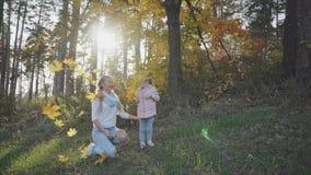 妇女和她的女儿投掷叶子,当走在秋天公园时 股票录像