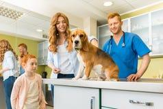 妇女和她的女儿有他们的狗的在兽医医生 库存图片