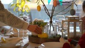 妇女和她的小女儿布置与兔宝宝的复活节欢乐桌并且怂恿装饰 股票视频