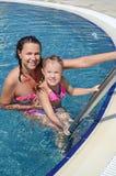 妇女和她的小逗人喜爱的女儿获得一个乐趣在水池 免版税图库摄影