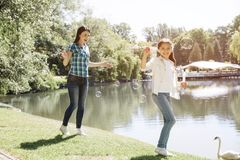 妇女和孩子一起使用 女孩吹肥皂泡 妇女在她和微笑后走 他们是 库存照片