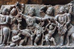 妇女和孩子与跳舞传统舞蹈在12世纪Hoysaleshwara寺庙的安心,印度的被破坏的面孔 免版税库存照片