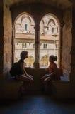 妇女和孩子剪影在树荫下,在一个窗口前面在阿维尼翁的教皇的宫殿 图库摄影