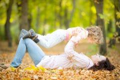 妇女和孩子在秋天公园 免版税库存照片