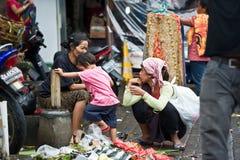 妇女和孩子在被污染的市场上在巴厘岛,印度尼西亚 库存照片