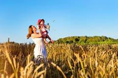 妇女和孩子金黄耳朵粮食作物的调遣 库存照片
