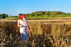 妇女和孩子金黄耳朵粮食作物的调遣 免版税库存图片