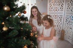 妇女和小女孩白色礼服的垂悬橙色球在圣诞树 库存照片