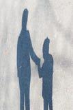 妇女和小孩子的阴影沥青的 免版税库存照片