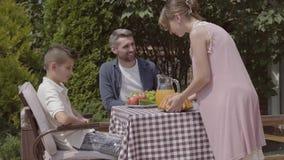 妇女和带来酥皮点心的女孩 坐在桌上的爸爸、妈妈和他们的两个孩子,吃在庭院享用的午餐 股票视频