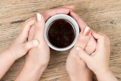 妇女和拿着咖啡的儿童手 库存照片