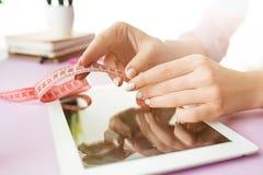 妇女和果子在办公室时节食,当研究计算机 库存图片