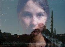 妇女和清真寺的反射在窗口里 免版税库存照片
