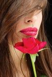 妇女和湿红色玫瑰在她的嘴唇附近 库存图片