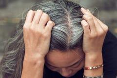 妇女和灰色头发有看担心的被注重的面孔的下来 免版税库存照片