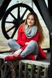 妇女和照相机的红色长袍poziruye前面在背景的 库存照片