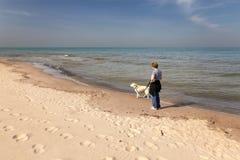 妇女和狗在海滩 库存图片