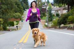 妇女和狗跑步 免版税图库摄影