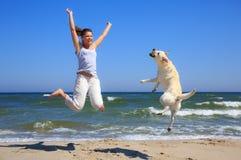 妇女和狗养殖跳在海滩的拉布拉多 免版税库存照片