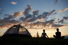 妇女和男孩剪影背面图坐与放松在露营地附近的野花的草在日落 免版税库存照片