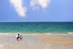 妇女和男孩在与蓝色海和清楚的天空的海滩使用 免版税库存图片