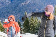 妇女和男孩在冬天山背景 愉快美丽 免版税库存图片
