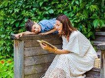 妇女和男孩在古老木门廊读一本书 免版税库存图片