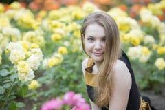 妇女和许多黄色玫瑰在她附近 免版税图库摄影