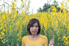 妇女和黄色猪屎豆属juncea L 背景山和t 库存图片