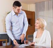 妇女和年轻未婚夫签署的婚姻财产契约 免版税库存图片