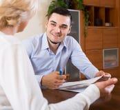 妇女和年轻未婚夫签署的婚姻财产契约 免版税库存照片