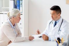 妇女和医生有处方的在诊所 免版税库存照片