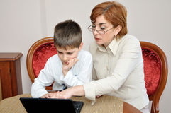 妇女和年轻男孩有膝上型计算机的 库存图片