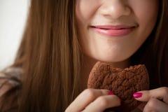 妇女品尝可口曲奇饼 免版税库存图片