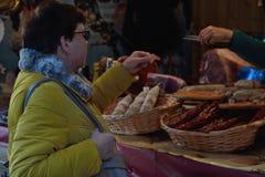 妇女品尝肉在一个地方市场上 免版税库存照片
