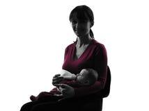 妇女哺乳瓶婴孩剪影 免版税图库摄影