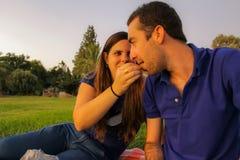 妇女哺养的人用在浪漫野餐的一个葡萄在日落 免版税库存图片