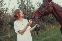 妇女喂养一匹马 免版税库存图片