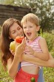 妇女喂养她儿子蔬菜 库存图片