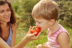 妇女喂养她儿子蔬菜 库存照片