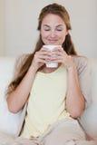 妇女喜欢嗅到在她新鲜的做的咖啡 免版税库存照片