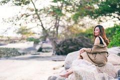妇女喜欢坐岩石由海滨 库存照片
