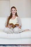 妇女喜欢读书在她的长沙发 免版税库存照片